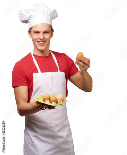 portrait of young cook man holding egg box over white background