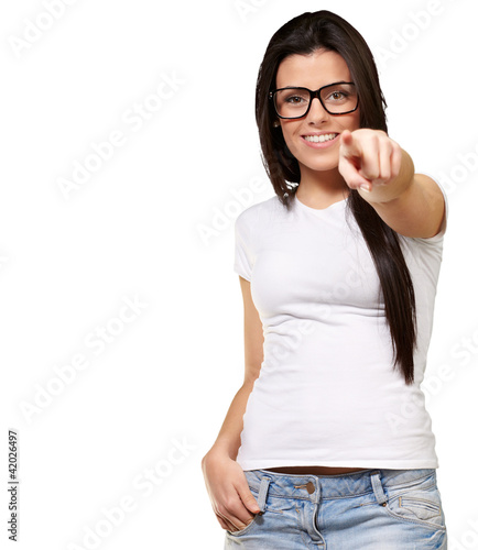 portrait of young woman pointing with finger against a white bac
