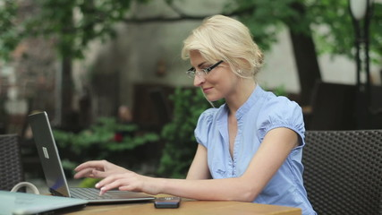 Successful businesswoman with laptop showing thumbs up