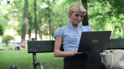 Young businesswoman working on laptop in the park