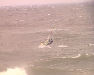 Brave windsurfers sailing between nasty stormy heavy sea waves