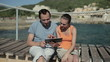 Couple with digital tablet sitting by the sea, tracking shot