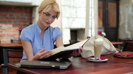 Young businesswoman reading menu in restaurant, steadicam shot
