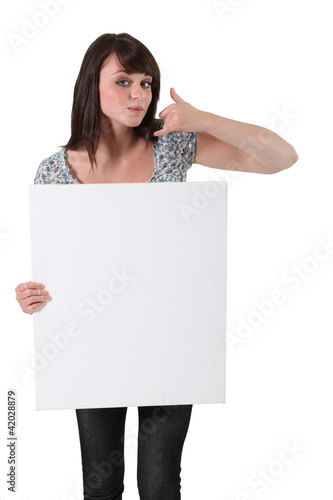 Brown-haired girl holding white panel for message