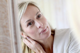 Attractive middle-aged woman applying comestics on her face poster