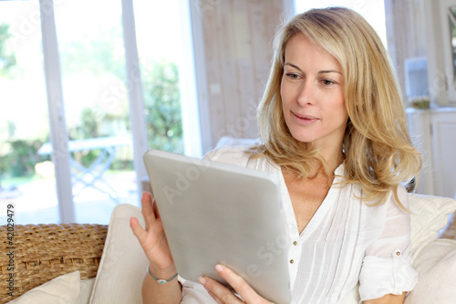 Beautiful mature woman using electronic tablet at home - 42029479