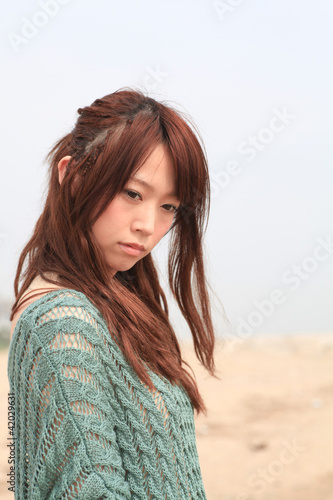 A young woman at beach / Long hair