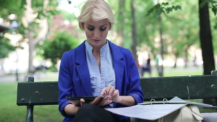 Businesswoman working with tablet and documents park,