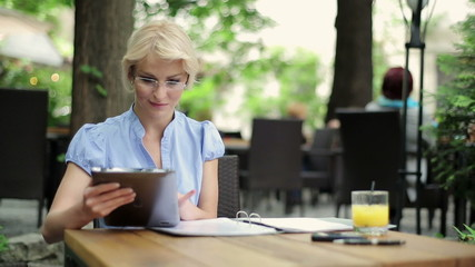 Businesswoman working with tablet and documents in cafe