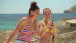 Two female friends  taking photo with cellphone
