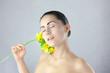 Piękna kobieta z żółtym kwiatkiem na srebrnym tle