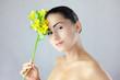 Twarz pięknej kobiety z uśmiechem i kwiatem w dłoni
