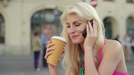 Woman talking on cellphone and drinking coffee in city