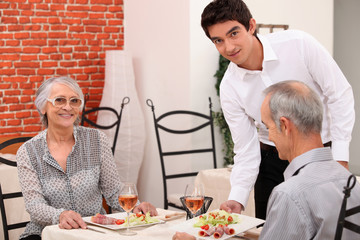 Waiter serving a senior couple