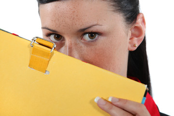 Woman hiding behind a folder