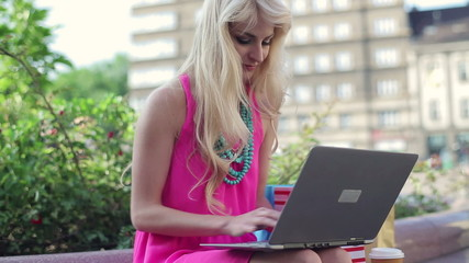 Attractive woman working on laptop in the city, steadicam shot