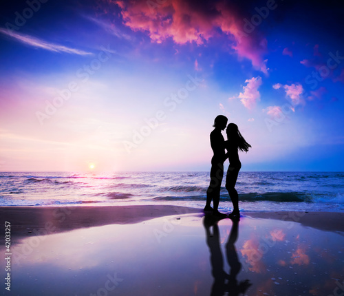 Romantic couple in love on beach at sunset