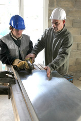 Apprentice being shown how to cut sheet metal