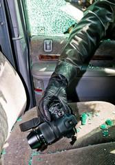 Ein Dieb entwendet eine Kamera aus Auto