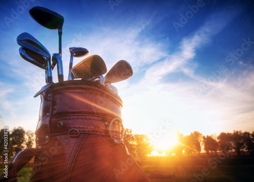 Golf gear, clubs at sunset on golf course