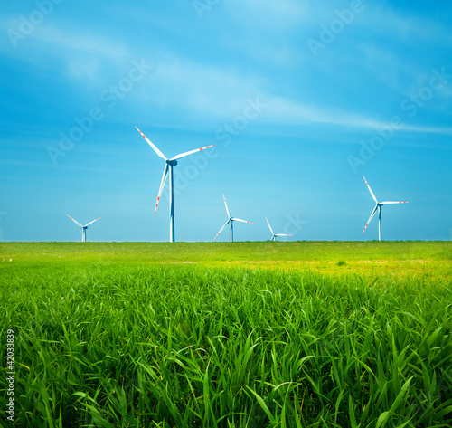 Wind turbines on green field. Clean energy