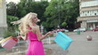 Happy woman with shoping bags in city, slow motion