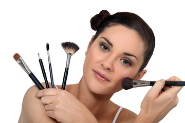 Brunette holding a selection of make-up brushes