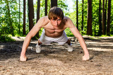 Attractive man doing a push up in forest