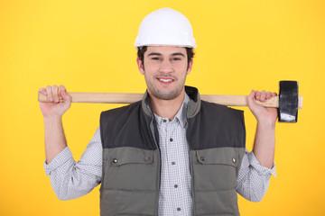 craftsman holding a huge hammer on his shoulders