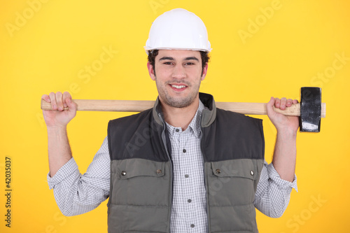 craftsman holding a huge hammer on his shoulders