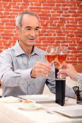 Senior man raising a glass in a restaurant