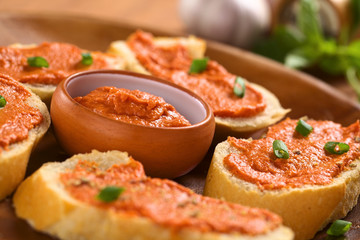 Tomato-butter spread in bowl with sandwiches around
