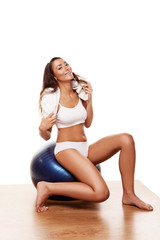 Sexy young female using a pilates ball and smiling