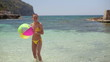 Happy woman throwing beach ball into camera lens, slow motion