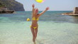 Girl playing with a beach ball on the shore, slow motion