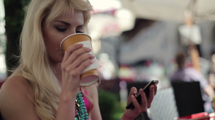 Woman using smartphone and drinking coffee in cafe