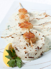 White and wild rice with fish grilled on a stick