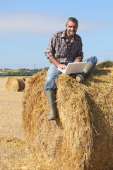 Farmer with a laptop sitting on a haystack
