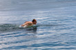 young sporting man swims in the sea dolphin style. ..