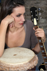 Moody brunette holding guitar and bongo