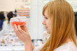 Blonde girl wearing white shirt looks at red caviar in store