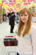 Blonde girl wearing white shirt with empty cart;