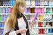 Blonde girl wearing white shirt chooses shampoo in large store;
