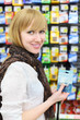 Blonde girl wearing scarf holds battery in shop;