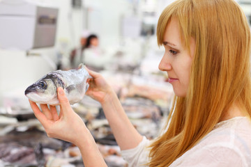 Blonde girl wearing white shirt holds fish in store