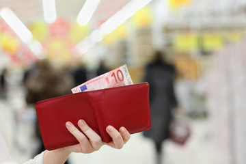 Woman hands keep red purse with money in shop