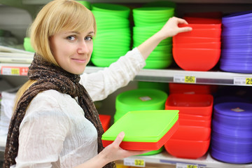 Smiling girl wearing scarf chooses colored plates in shop