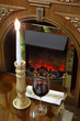 glass with wine and burning candle at table in restaurant