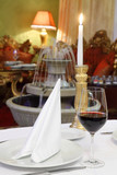 glass with wine, white napkin and candle at table