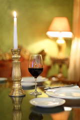 glass with wine and candlestick with candle at table